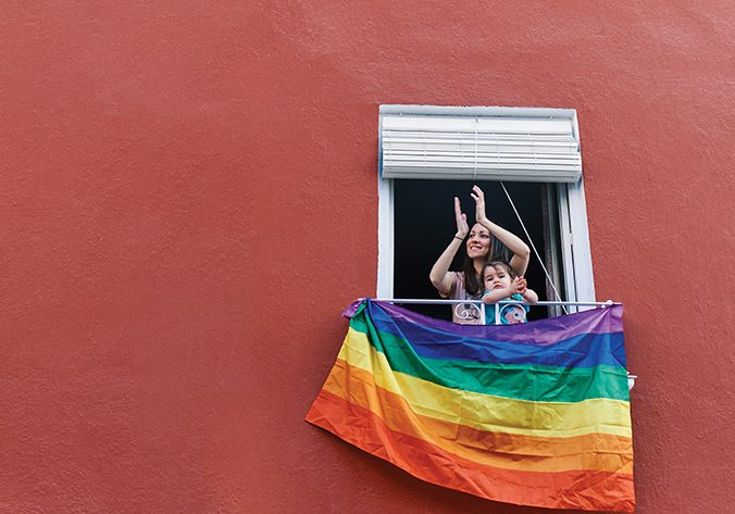 young woman in a mask clapping from the window with the gay flag on a red background